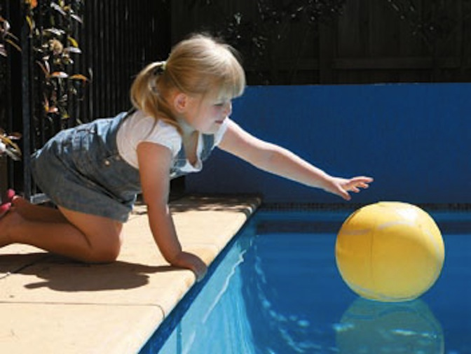 Image of child reaching for a ball over a swimming pool