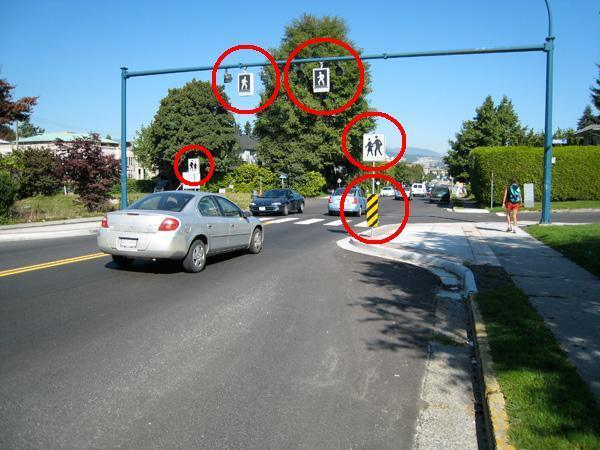 Image of a crossing in Vancouver features kerb extensions and zebra stripes, signage and amber pedestrian activated lights, hung overhead, to help motorists identify this as a crossing. Also, there are hazard signs to warn motorists that the road narrows between the kerb extensions